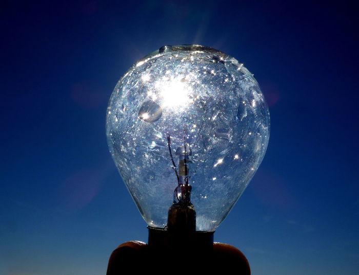 Cropped hand holding light bulb against blue sky