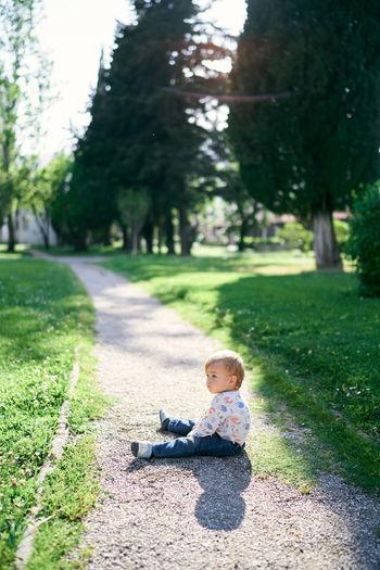 Boy sitting on footpath