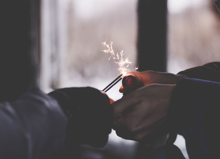 Cropped hands of person holding lit sparklers