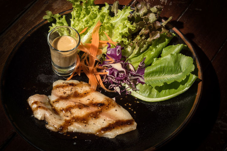 Fish steak with vegetable salad on plate Close-up Food Food And Drink Freshness Fruit Glass Healthy Eating High Angle View Household Equipment Indoors  Lettuce Meat No People Plate Ready-to-eat Refreshment Salad Still Life Vegetable Wellbeing
