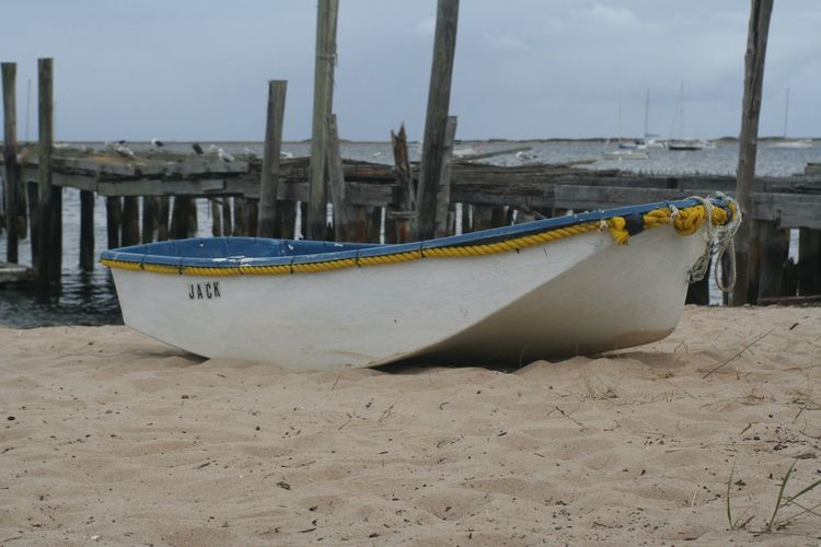 Boat moored on sandy beach with pier on sea
