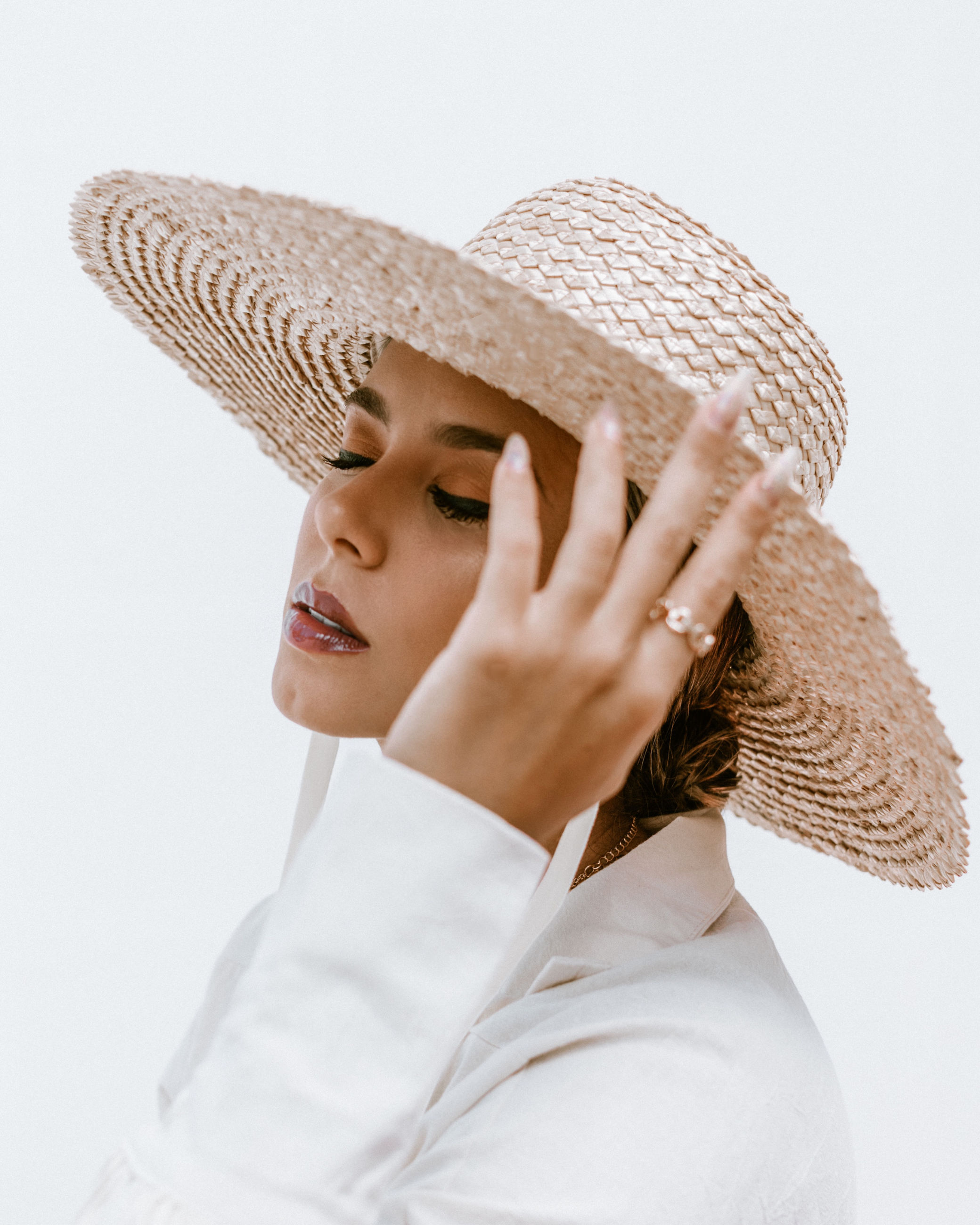 one person, hat, women, adult, portrait, clothing, fashion accessory, cap, studio shot, young adult, sun hat, headshot, indoors, straw hat, female, fashion, sombrero, headgear, hand, white background, human face, waist up, looking