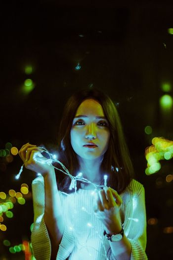 Portrait Of Beautiful Woman Holding Illuminated String Lights At Night