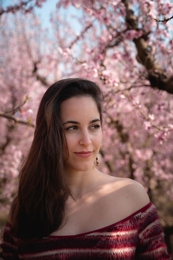 Portrait of beautiful woman with pink flower against trees