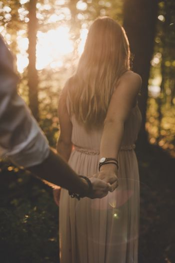 Rear View Of Woman Holding Hands With Man In Forest During Sunset