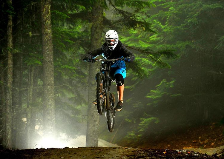 Man Performing Stunt With Bicycle Against Trees