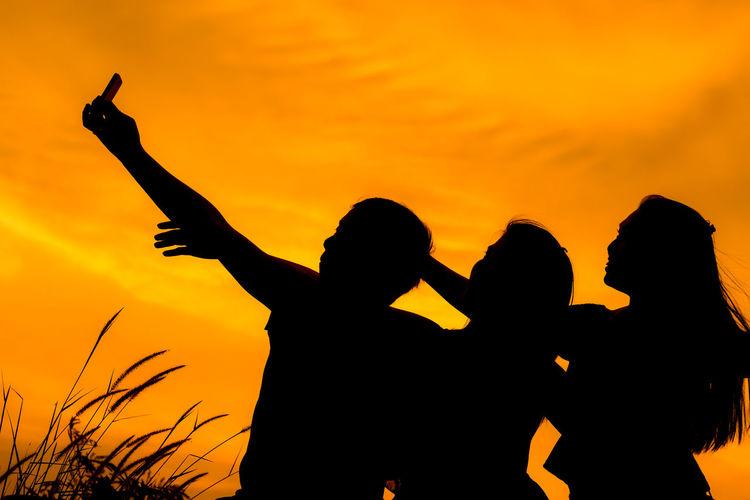 Silhouette friends taking selfie against orange sky