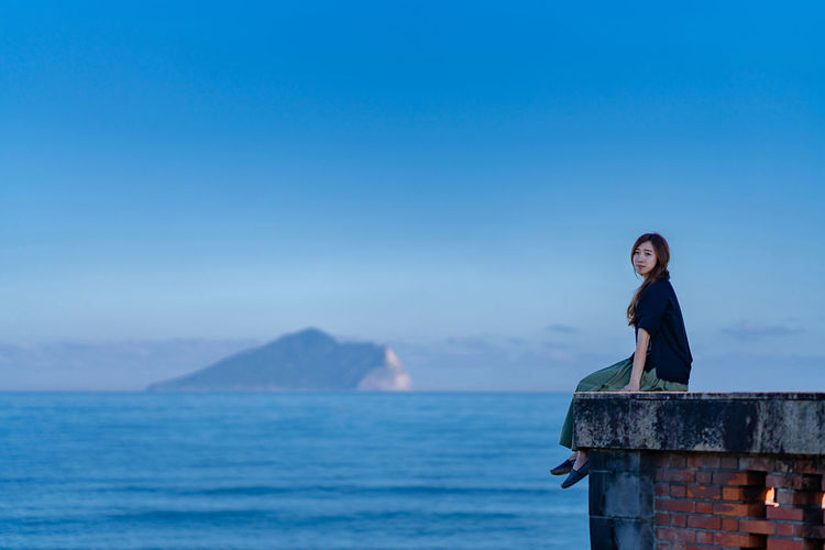 Side view portrait of young woman sitting on building terrace by sea against blue sky