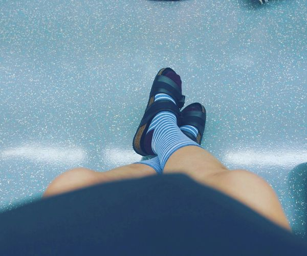 Low section of woman wearing socks and sandals resting on blue floor