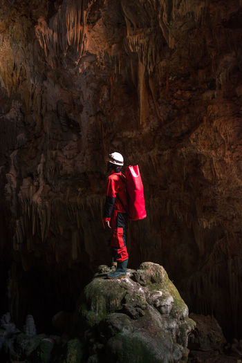 Rear view of man standing on rock in cave