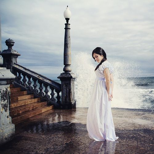 Beautiful young woman by staircase at promenade
