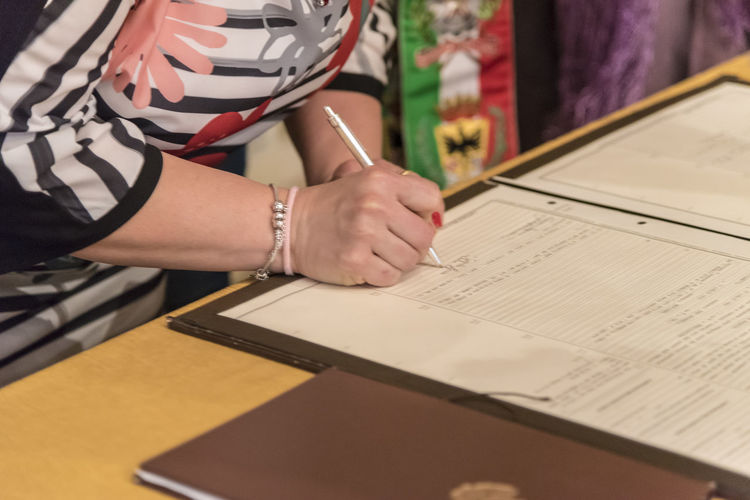 Midsection of woman signing on paper at home