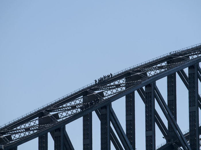 Silhouette people at sydney harbor bridge against clear sky