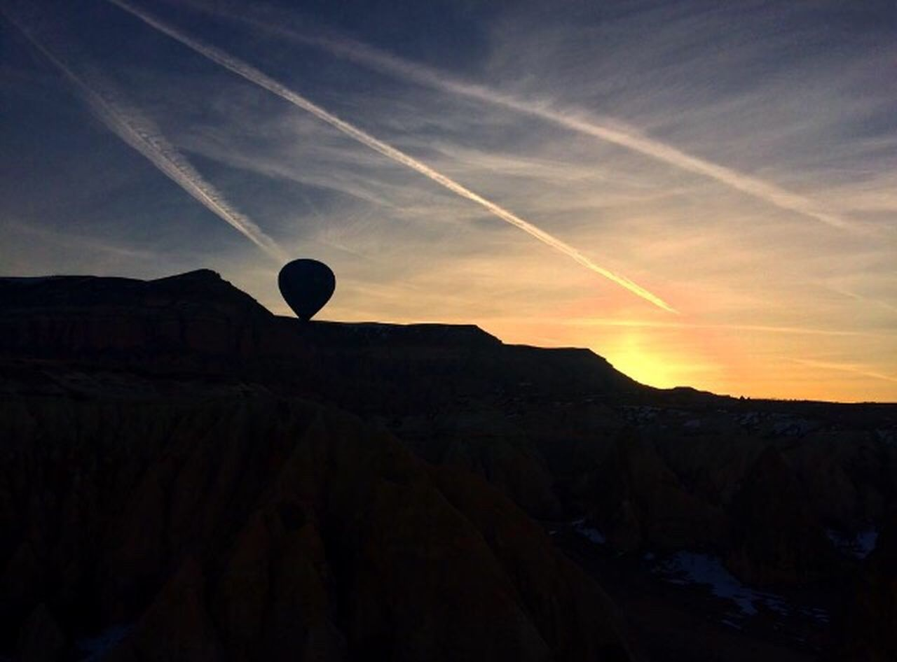 sunset, nature, beauty in nature, tranquil scene, scenics, tranquility, outdoors, silhouette, mountain, landscape, no people, sky, hot air balloon, day, vapor trail, astronomy