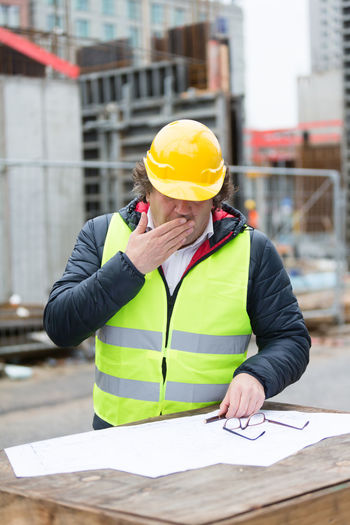 Engineer covering mouth while yawing at construction site