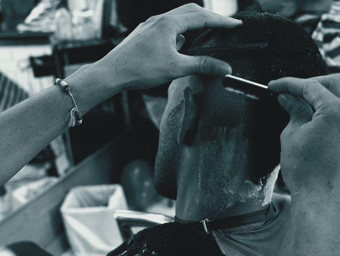 Close-up of barber shaving man head