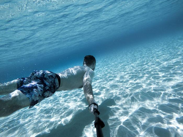 Go pro selfie of man swimming underwater