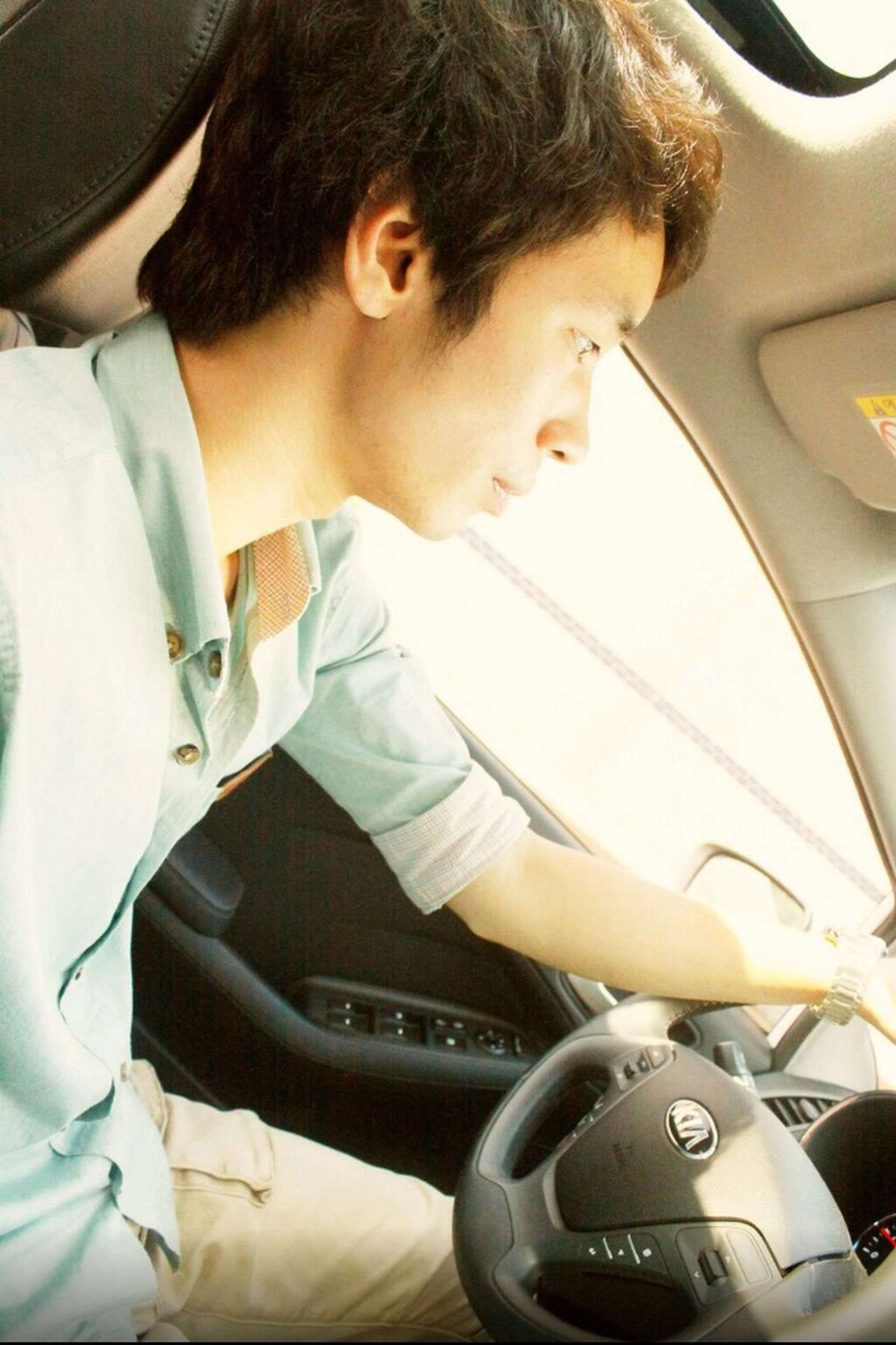 indoors, lifestyles, young adult, vehicle interior, person, sitting, transportation, leisure activity, mode of transport, wireless technology, technology, casual clothing, young men, car, connection, car interior, land vehicle, vehicle seat