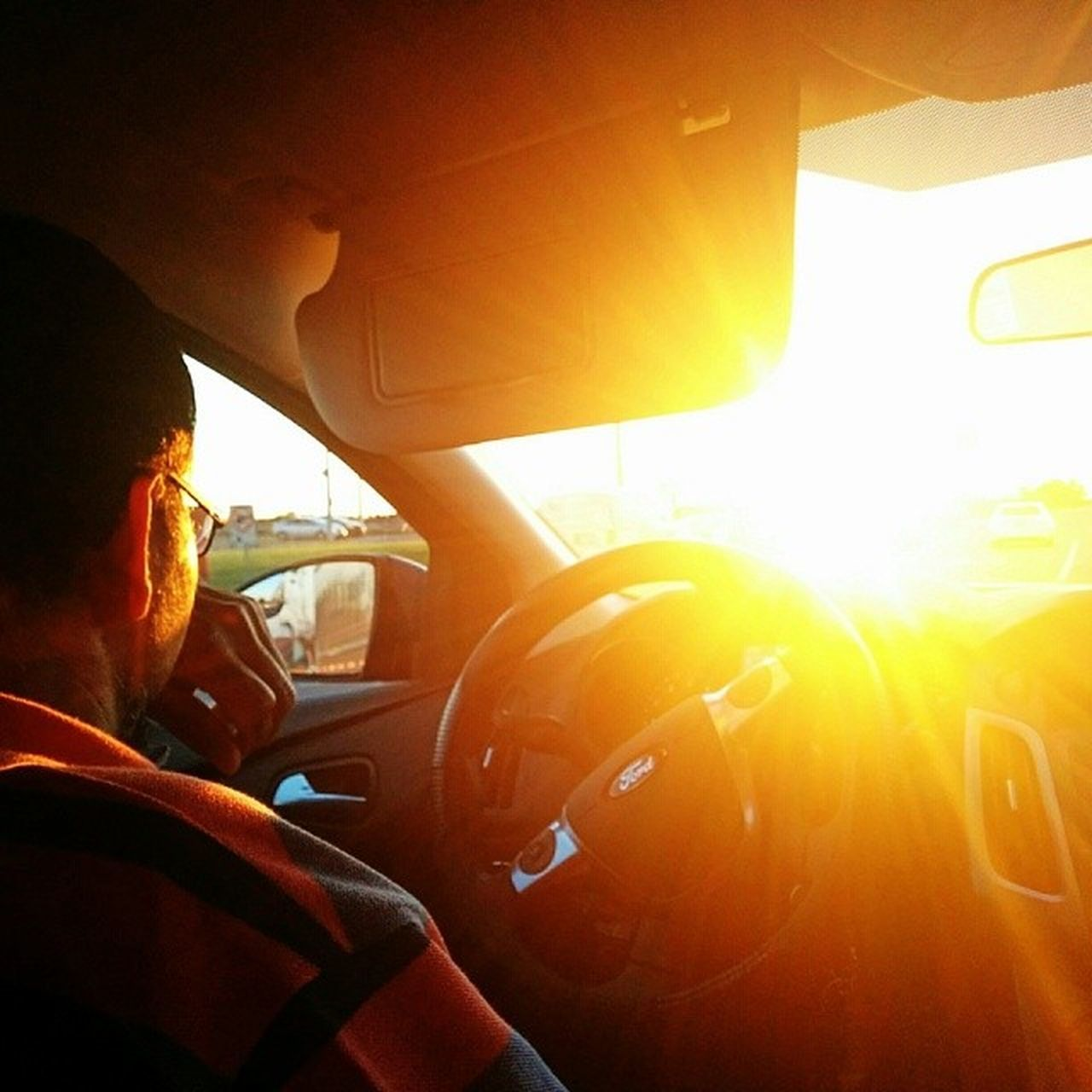 car, vehicle interior, car interior, transportation, land vehicle, driving, mode of transport, steering wheel, real people, one person, windscreen, windshield, men, human hand, dashboard, sunlight, day, lifestyles, outdoors, close-up, people