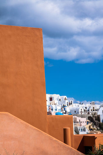 Buildings Against Cloudy Blue Sky At Oia