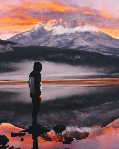 Man Standing On Rock In Sparks Lake Against Mountain During Sunset