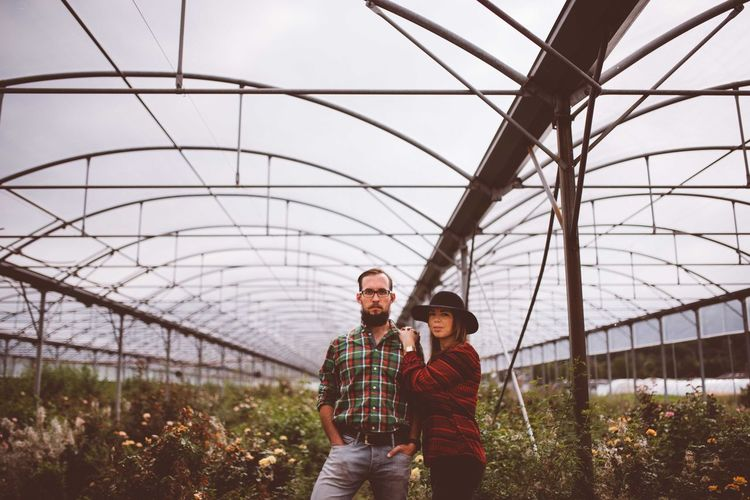 Portrait of couple standing in greenhouse