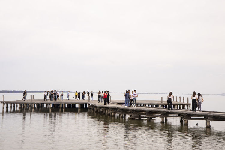 Group of people on pier against clear sky