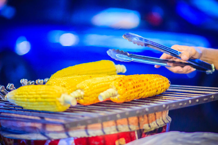 Close up hand of street food vendor while grilling for mixed sweet corn butter. Cook is grilling and sprinkling salt, sugar and butter to the grilled sweet corn on the electric stove. Grilled Corn Khao San Rd Khao San Road KhaoSan Khaosan Rd. Khaosandroad Khao San Khao San Knok Wua Khao San Rd. Khaosan Road Khaosanroad Night Market Night Market In Thailand Sprinkling Salt