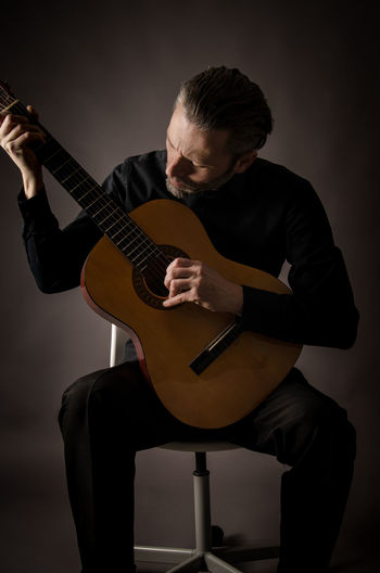 Male musician playing guitar while sitting on chair against black background