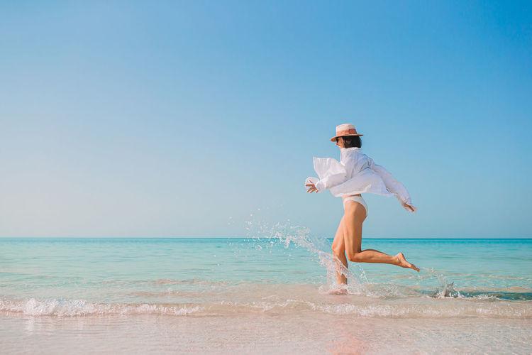 Full length of woman running at beach