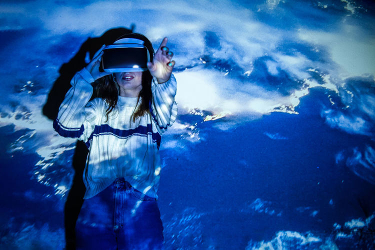 Young woman wearing virtual reality simulator standing against blue background