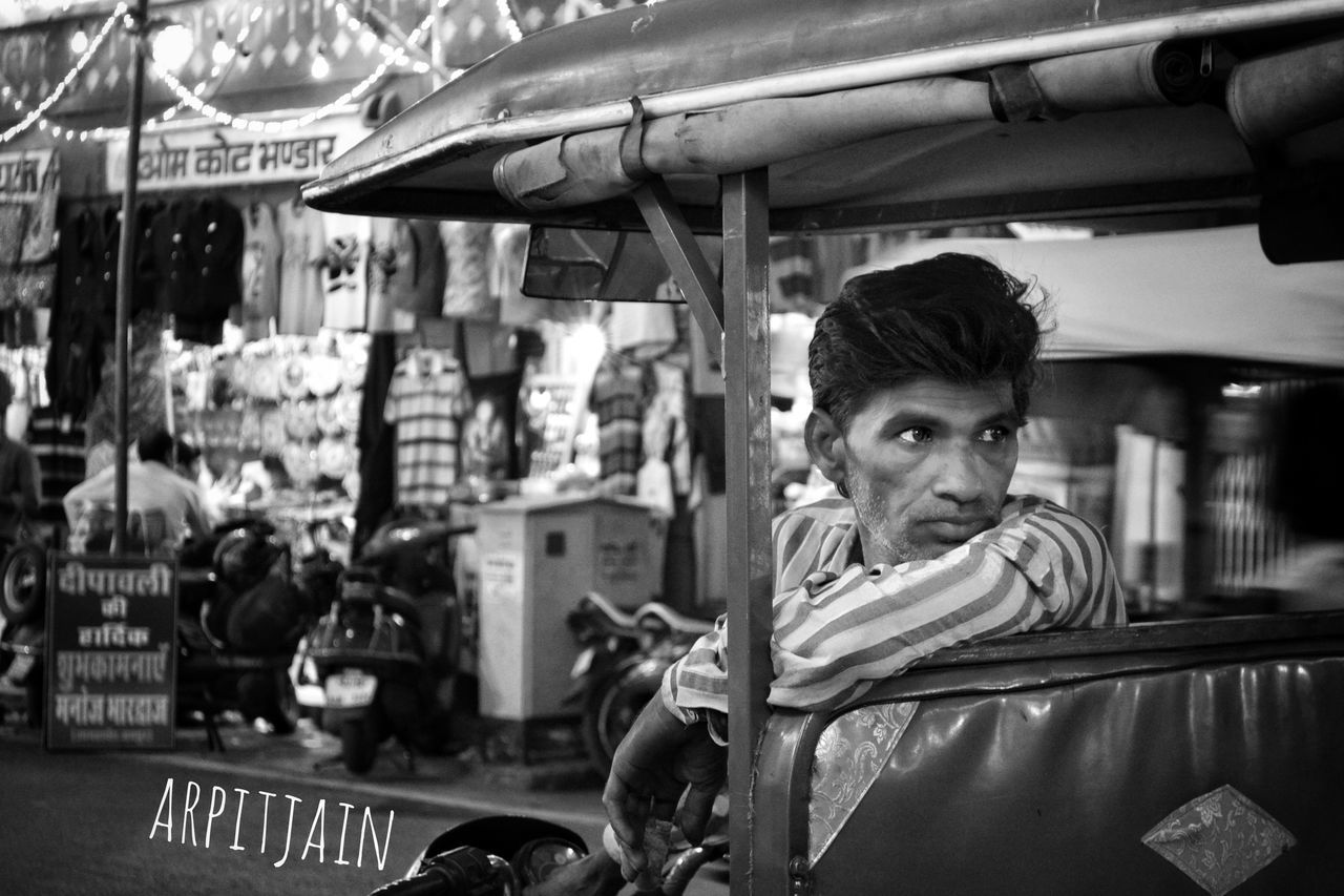 real people, one person, leisure activity, young men, lifestyles, young adult, mode of transport, front view, transportation, land vehicle, outdoors, looking at camera, day, sitting, portrait, carousel, people