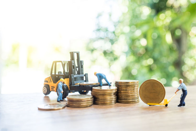 Close-up of figurines with toy forklift with coins on table