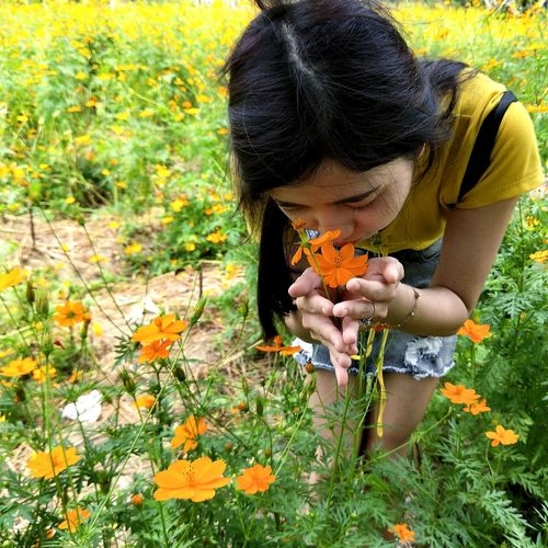 Close-up of girl holding flowers on field