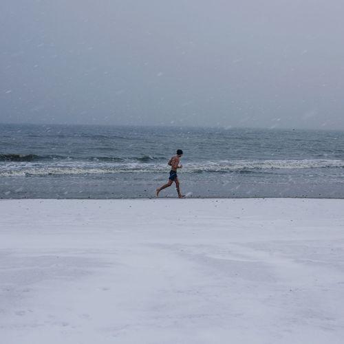 Full length of man jogging on shore at beach against sky