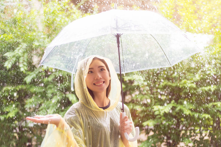 Smiling Young Woman Holding Umbrella During Rainfall