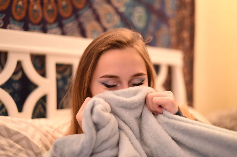 Close-up of teenage girl holding blanket on bed at home