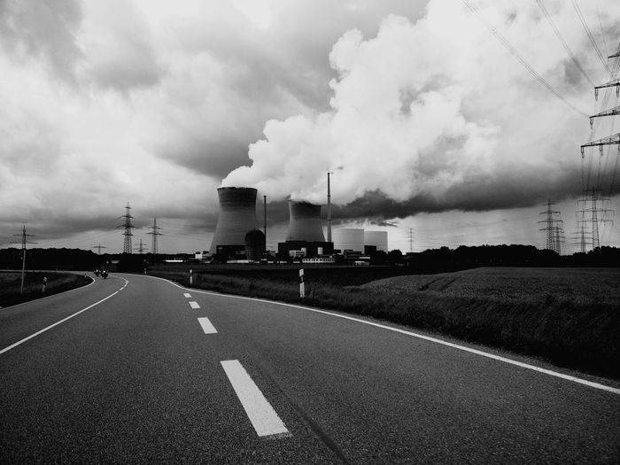 Country road by silos emitting pollution against cloudy sky