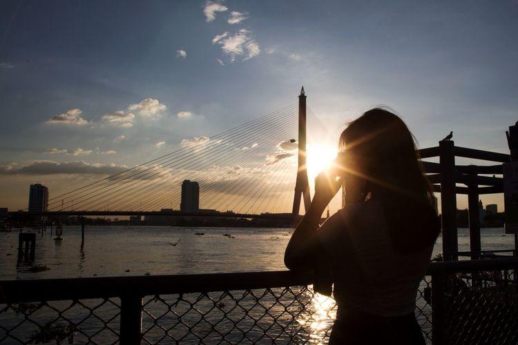 Man standing on bridge over river against sky during sunset