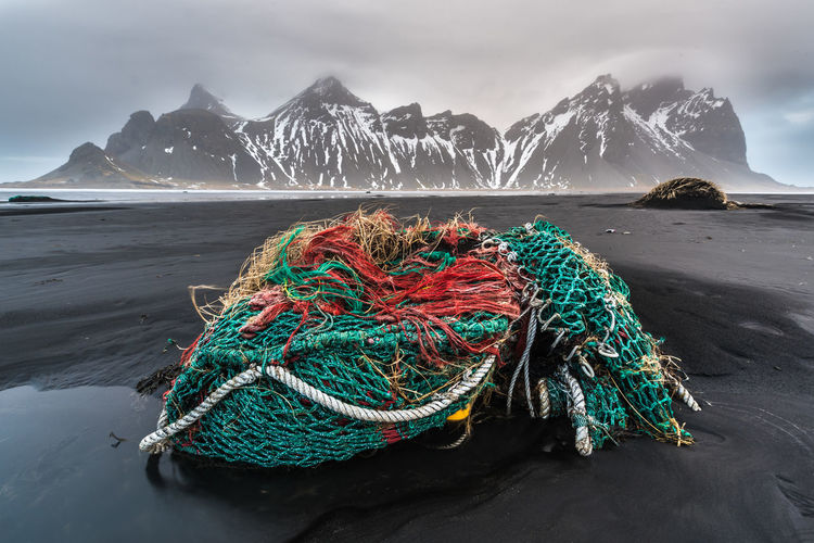 View Of Fishing Net  On Beach Against Mountains
