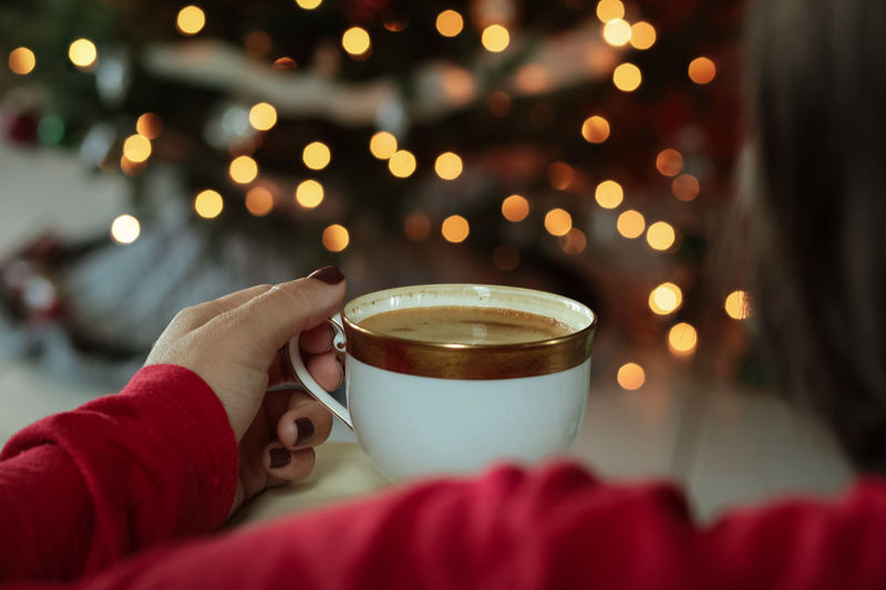 Woman holding coffee cup in front of chistmas tree