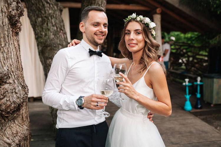 Portrait of couple with arm around holding wineglasses while standing outdoors
