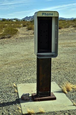 abandoned empty phone booth remains standing isolated in desert landscape as sign of bygone times when communications technology such as this phone booth held coin operated large telephone call vending machines Desert Old Fashioned Old Technology Old Telephone Booth Vending Machine Hell Abandoned Close-up Communication Day Design No People Outdated Tech Outdoors Pay Phone Phone Booth Vending Machine