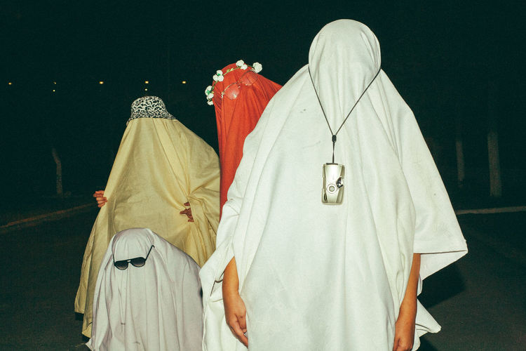 People wearing costume standing outdoors at night