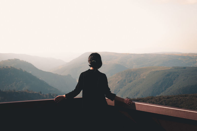 Man sitting on mountain against clear sky
