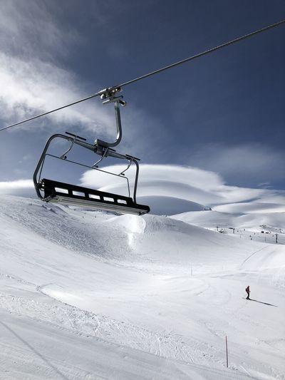 Ski lift over snowcapped mountains against sky
