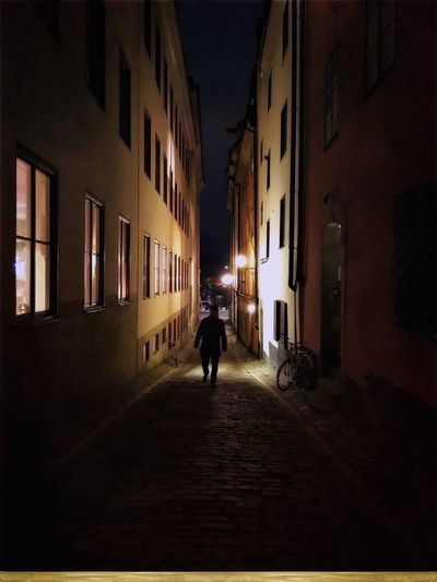 Man walking on illuminated street at night