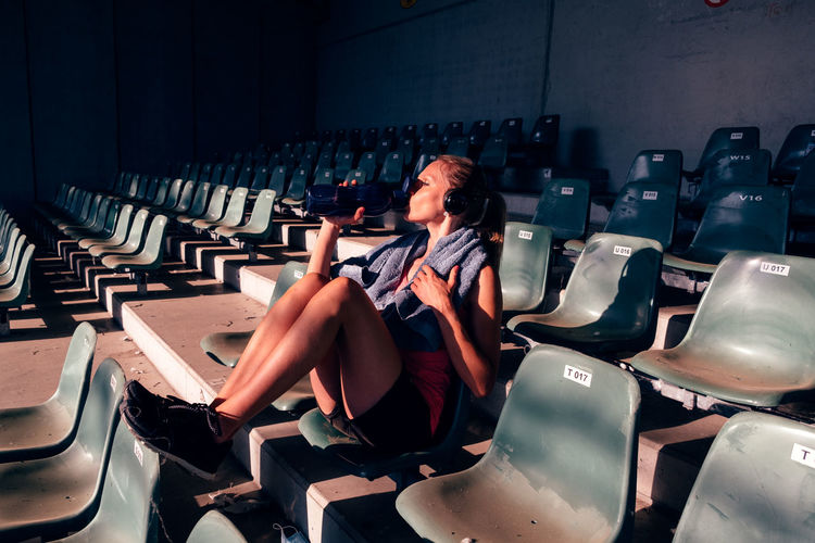 Athletic woman taking rest after workout - fit woman in sportswear sitting on stadium seats