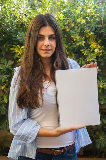 Portrait of woman holding spiral notebook against plants