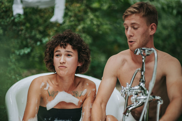 Portrait of shirtless man and woman looking at camera